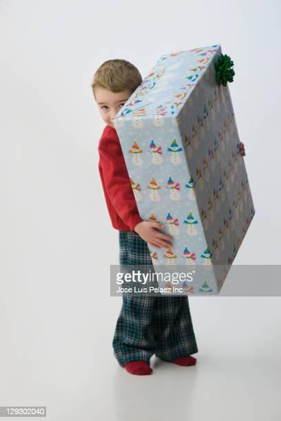 Caucasian boy holding large Christmas gift