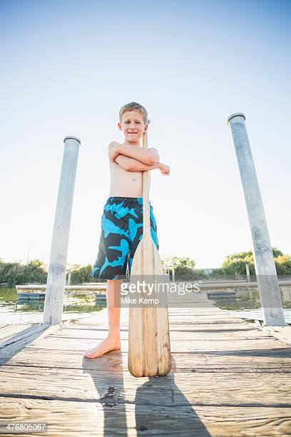 Caucasian boy holding paddle on dock