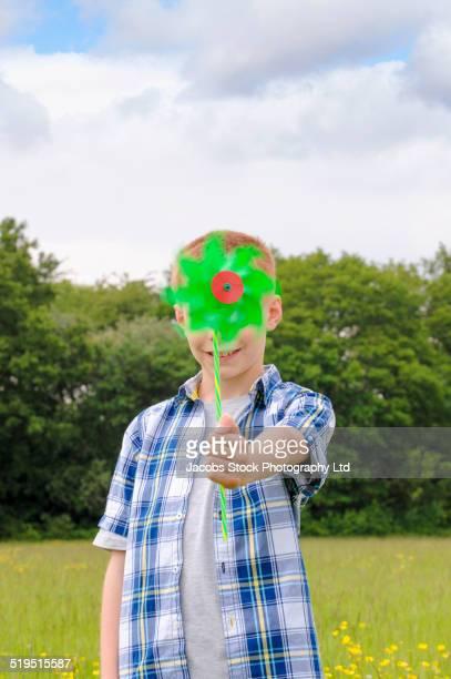 Caucasian boy holding pinwheel in field