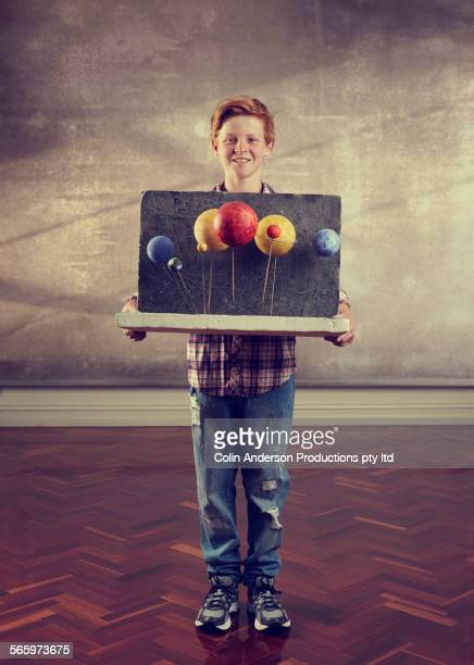 Caucasian boy holding science diorama