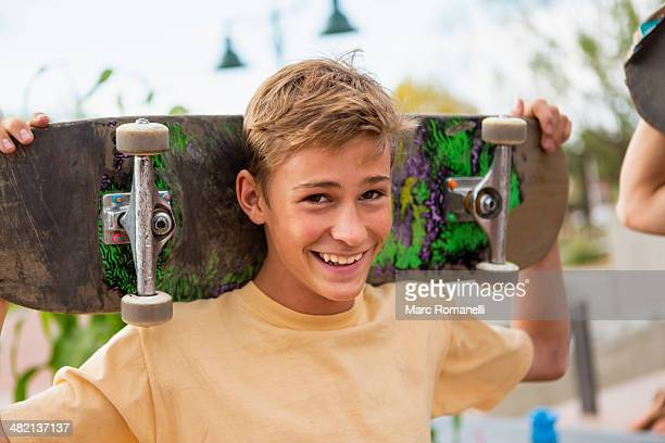 Caucasian boy holding skateboard outdoors