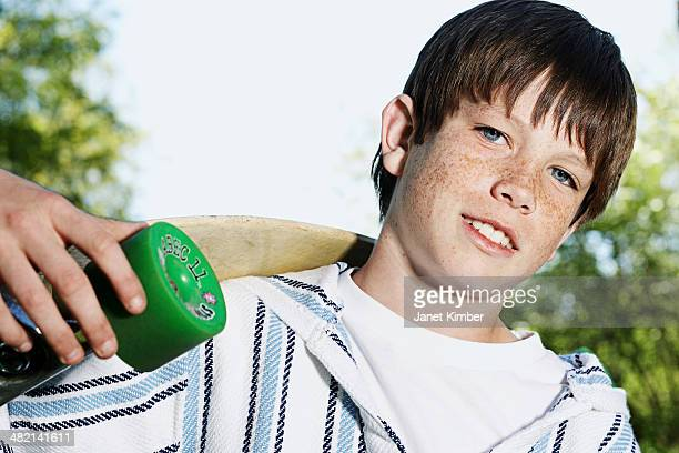 Caucasian boy holding skateboard outdoors
