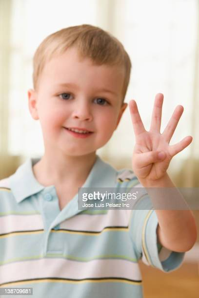 Caucasian boy holding up four fingers