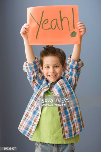 Caucasian boy holding up sign that says 'yeah!'