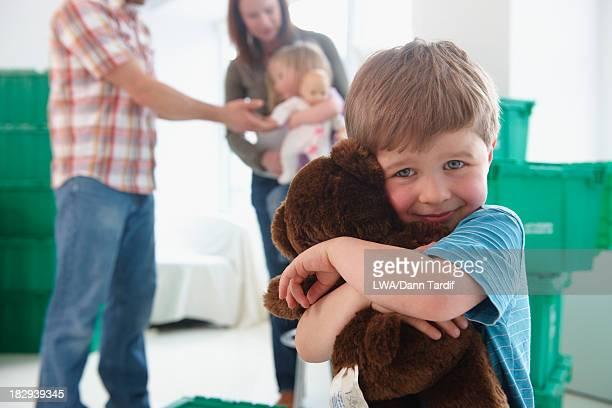 Caucasian boy hugging teddy bear in new home