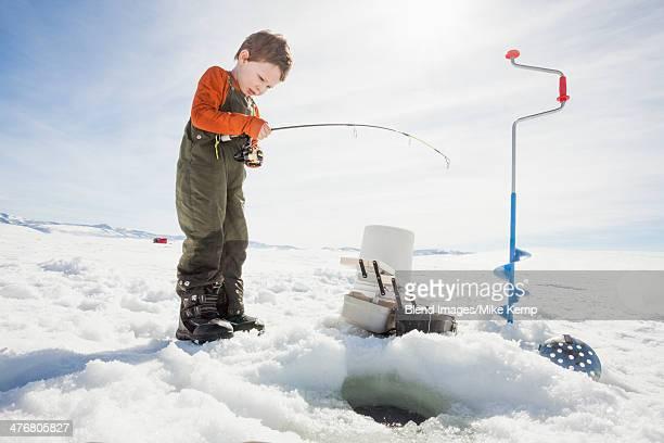 Caucasian boy ice fishing