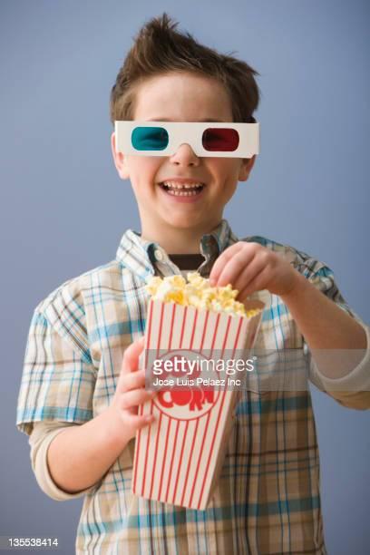 Caucasian boy in 3-D glasses eating popcorn