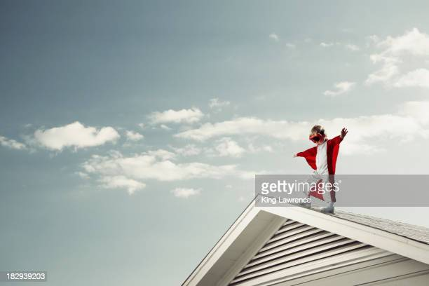 caucasian boy in cape at edge of roof - danger stock photos and pictures