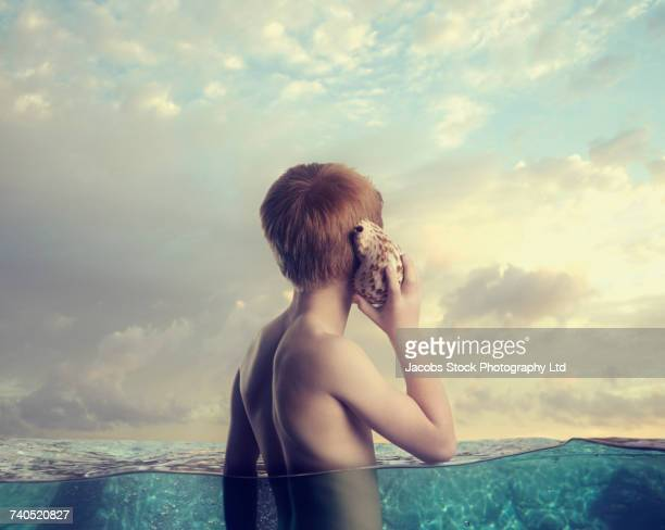 Caucasian boy in ocean listening to seashell