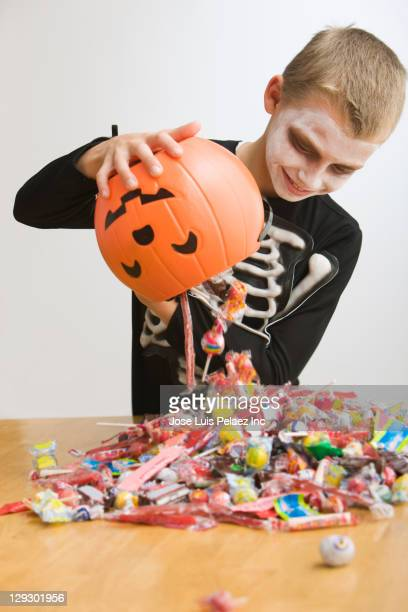 caucasian boy in skeleton dumping out halloween candy - pile of candy stock photos and pictures