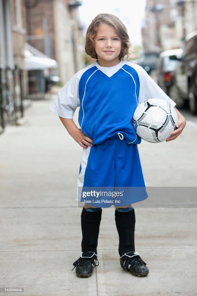 Caucasian boy in soccer uniform holding ball : Stock Photo