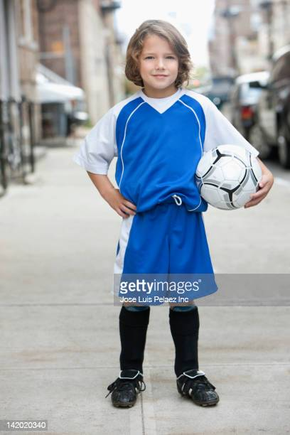caucasian boy in soccer uniform holding ball - fußballtrikot stock-fotos und bilder