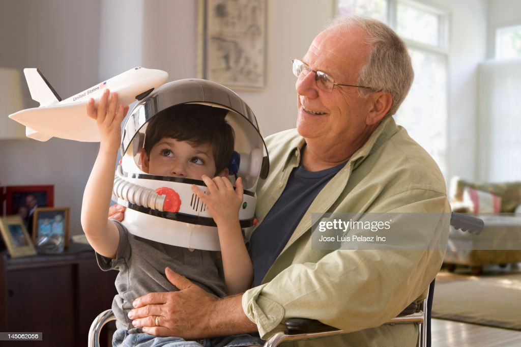 Caucasian boy in space helmet sitting on grandfather's lap : Stock Photo