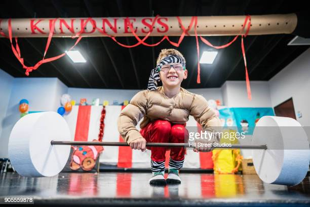 Caucasian boy in strongman costume lifting toy barbell
