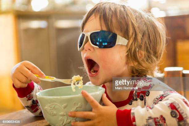 caucasian boy in sunglasses eating in kitchen - rébellion photos et images de collection