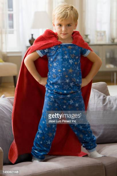caucasian boy in superhero costume standing on sofa - lichaamshouding stockfoto's en -beelden