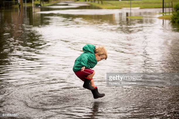Caucasian boy jumping in puddle