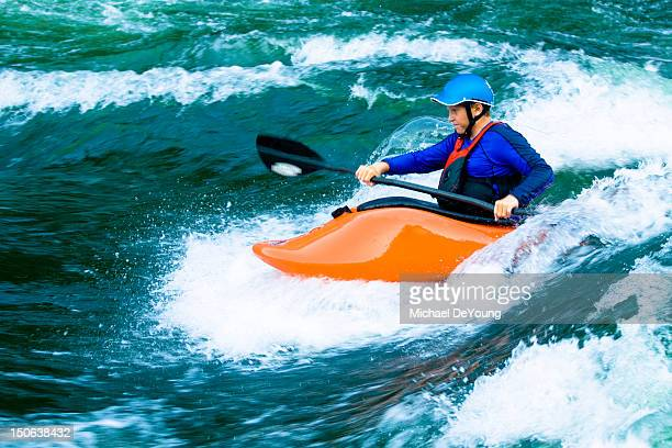 Caucasian boy kayaking on river