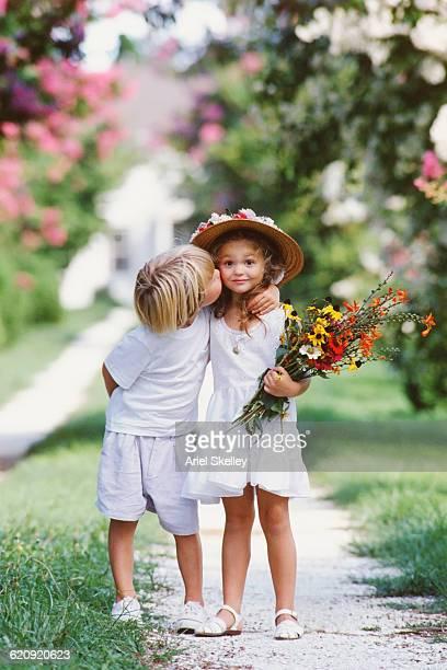 Caucasian boy kissing girl on cheek