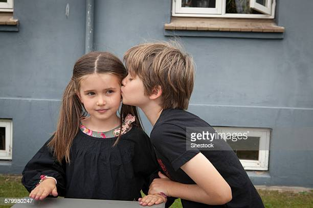 Caucasian boy kissing sister in backyard