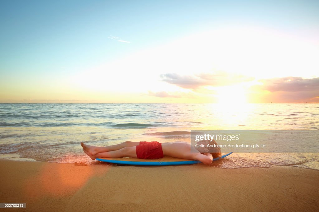 Caucasian Boy Laying On Surfboard On Beach Stock Photo ...