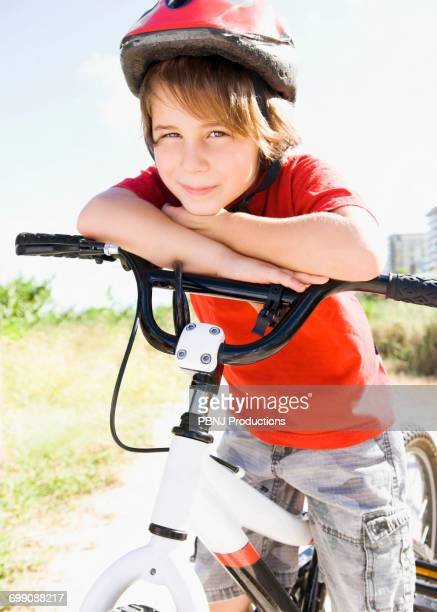 Caucasian boy leaning on bicycle handlebar