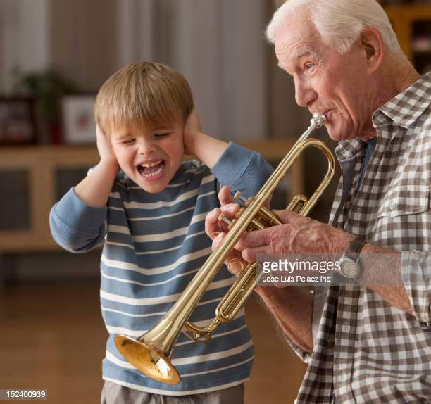 caucasian boy listening to grandfather playing trumpet - tromba foto e immagini stock