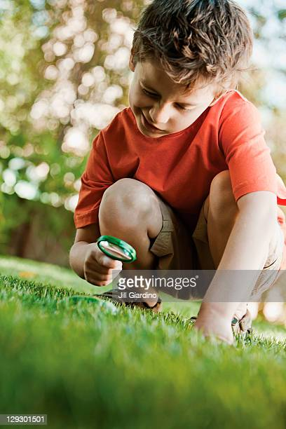 Caucasian boy looking at grass with magnifying glass