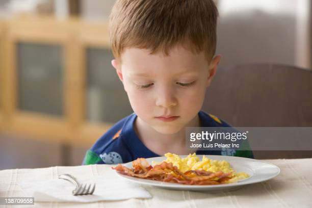 caucasian boy looking at plate of eggs and bacon - refusing stock pictures, royalty-free photos & images