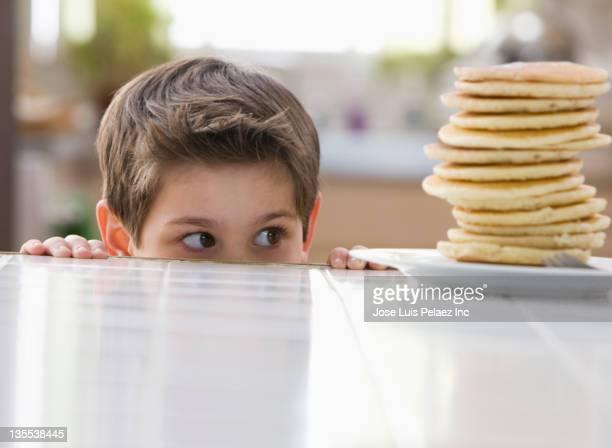 Caucasian boy looking at stack of pancakes