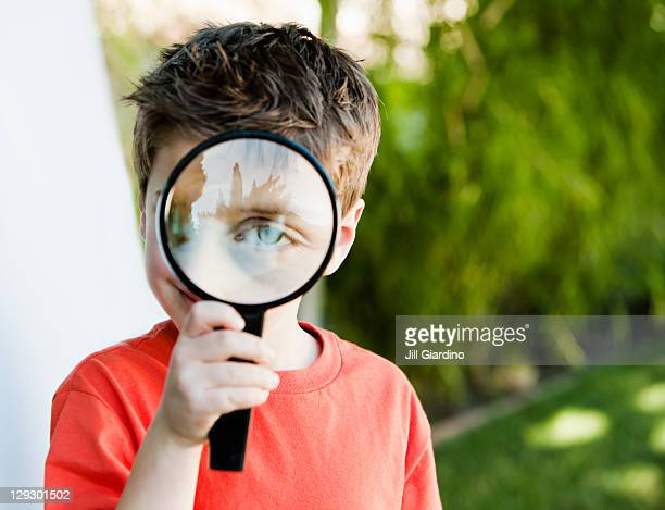 Caucasian boy looking through magnifying glass
