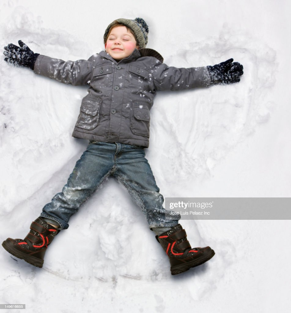 Caucasian boy making snow angel : Stock Photo