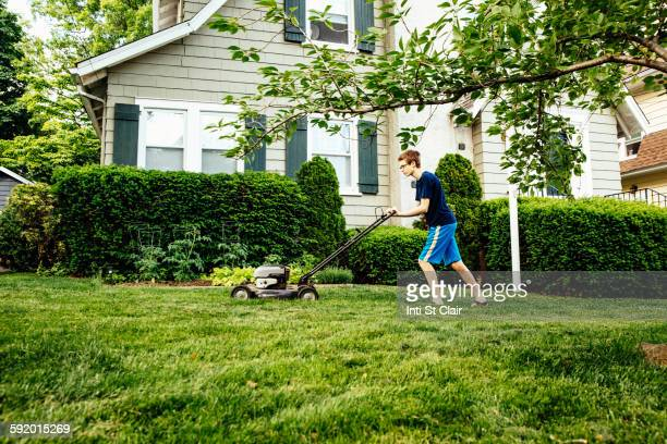 caucasian boy mowing front lawn - lawn mower stock pictures, royalty-free photos & images