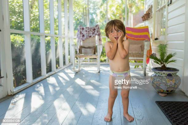 Caucasian boy on the porch wearing a diaper