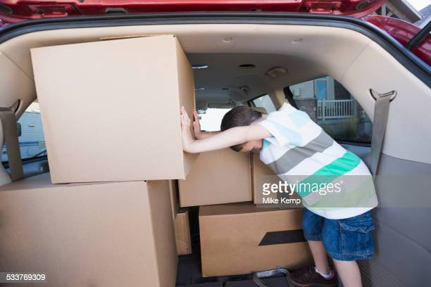 Caucasian boy packing cardboard boxes in car