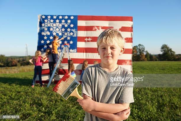 Caucasian boy painting American flag in field