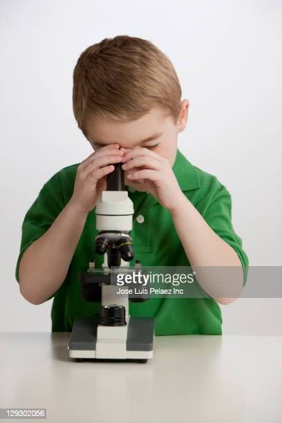 Caucasian boy peering into microscope