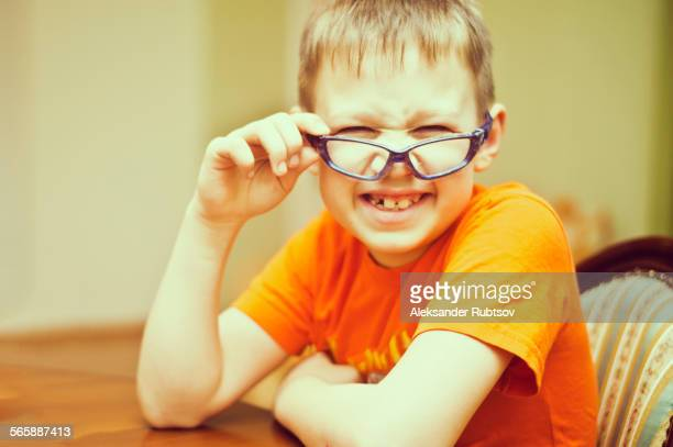 Caucasian boy peering over glasses