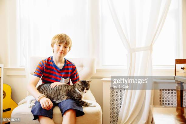 Caucasian boy petting cat in living room