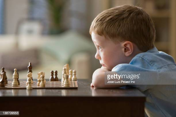 caucasian boy playing chess - chess stock pictures, royalty-free photos & images