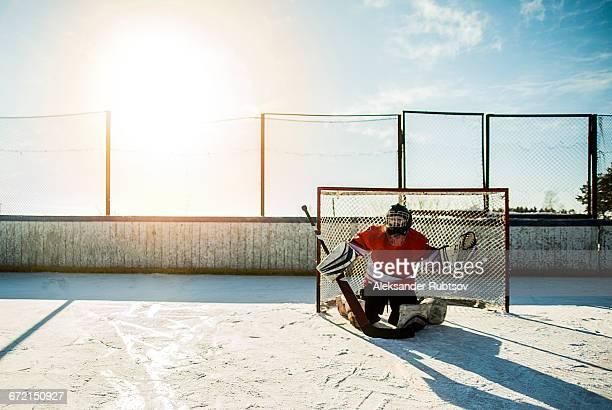 caucasian boy playing goalie in ice hockey outdoors - doelman ijshockeyer stockfoto's en -beelden