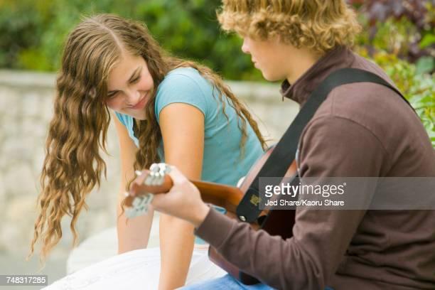 Caucasian boy playing guitar for girl