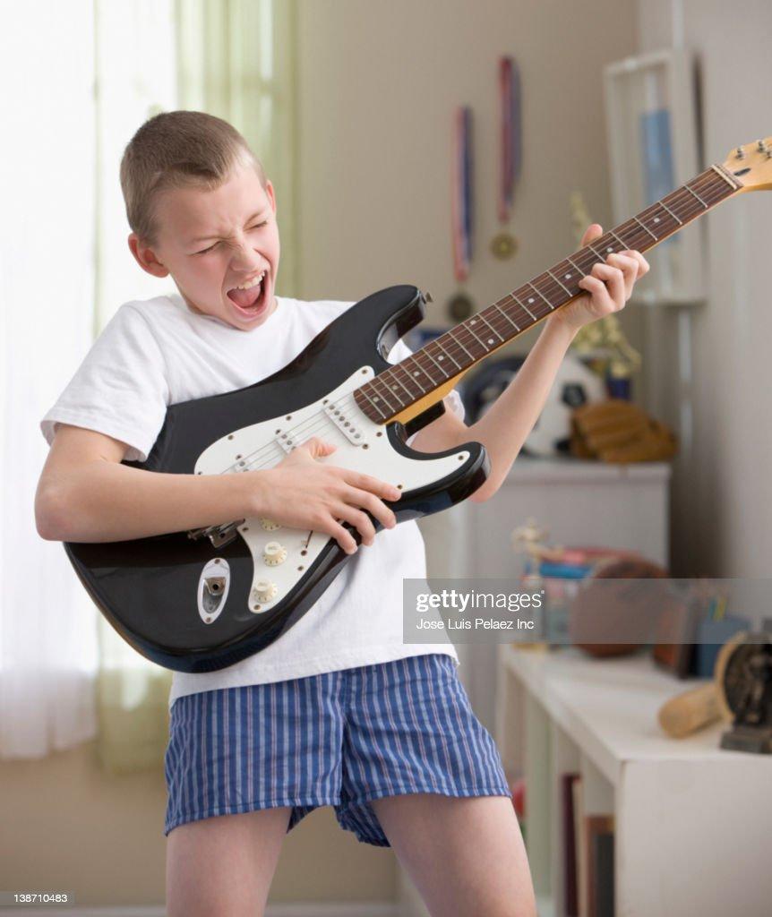 Caucasian boy playing guitar : Stock Photo