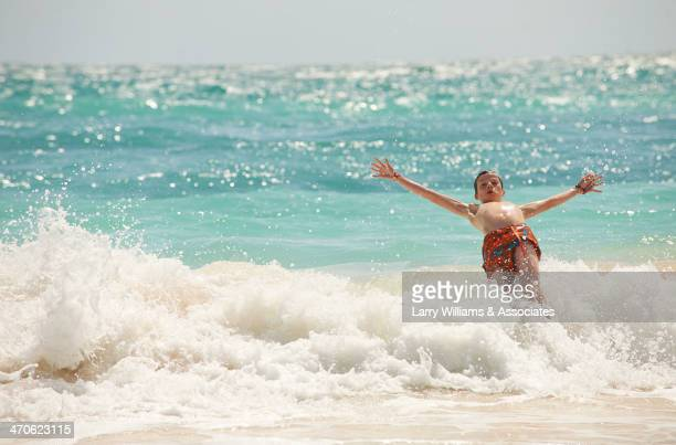 Caucasian boy playing in waves on beach