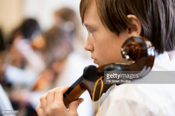 Caucasian boy playing instrument in music class