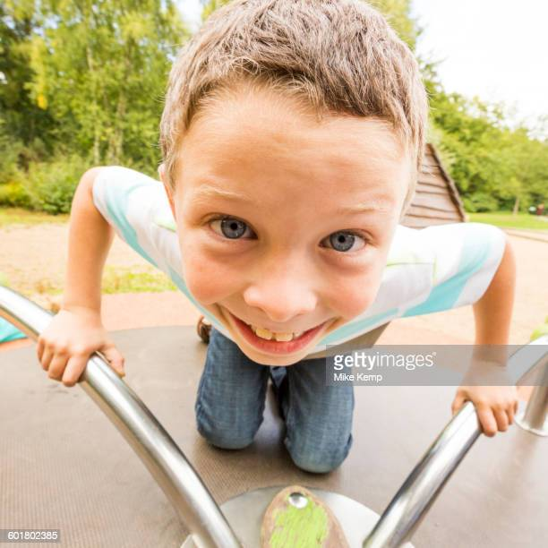 Caucasian boy playing on merry-go-round