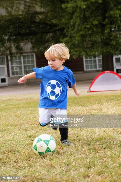 Caucasian boy playing soccer in field