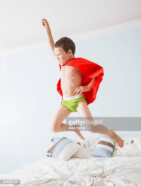 Caucasian boy playing superhero on bed