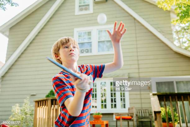 Caucasian boy playing table tennis in backyard
