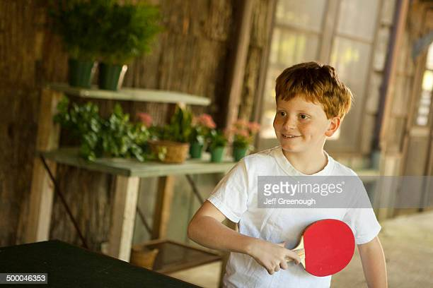 Caucasian boy playing table tennis